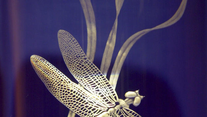FILE -  In this Sept 18, 2003 file photo shows intricate engraving on a piece called Dragonfly by Eric Hilton at the Steuben Glass store inside the Corning Museum of Glass in Corning, N.Y. Steuben Glass, an American icon of handcrafted crystal for over a century, looks now as if it's vanishing for good. Its lone factory in Corning, a glassmaking company in southwestern New York, is shutting down Nov. 29, the week after Thanksgiving. With profitability elusive at the best of times, the prospects of reviving the 108-year-old vanity brand seem every bit as slim. (AP Photo/David Duprey, file)
