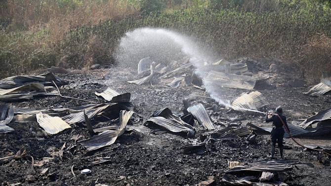 A firefighter douses a fire at a timber shop in Bhiwandi, India, Saturday, Dec. 27, 2014. The fire near the Indian financial capital of Mumbai early Saturday burnt eight people to death, police said. The victims were workers who were sleeping in the shop, said police officer Ramesh Patil. (AP Photo/Press Trust of India)