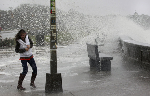 A woman reacts to waves crashing over a seawall in Narragansett, R.I., Monday, Oct. 29, 2012.  Hurricane Sandy continued on its path Monday, as the storm forced the shutdown of mass transit, schools a
