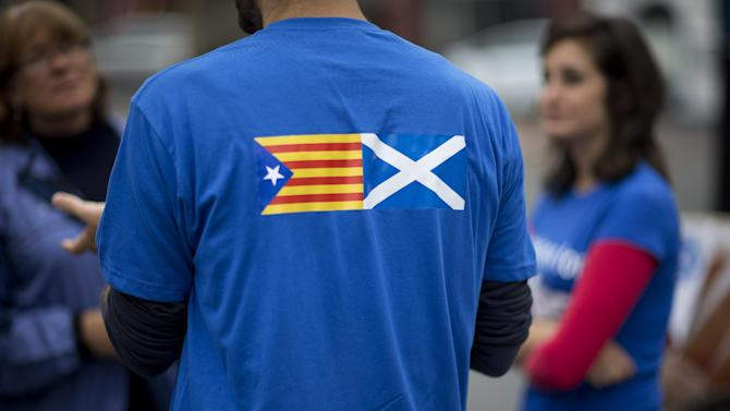 """David Aguilar who is visiting Scotland from Catalonia to support the Scottish independence referendum, wears a t-shirt printed with a design showing an """"estelada"""" Catalan pro-independence flag, left, next to a Scottish Saltire flag as he speaks to passersby in Edinburgh, Scotland, Thursday, Sept. 18, 2014.  Polls have opened across Scotland in a referendum that will decide whether the country leaves its 307-year-old union with England and becomes an independent state.  (AP Photo/Matt Dunham)"""