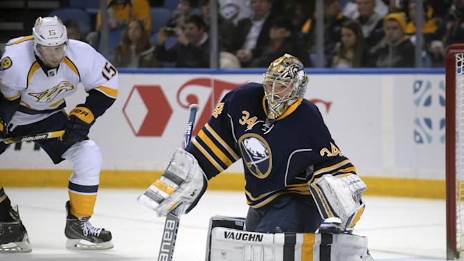FILE - In this Feb. 22, 2015, file photo, Buffalo Sabres goaltender Michal Neuvirth (34) and Nashville Predators center Craig Smith (15) watch the puck during an NHL hockey game in Buffalo, N.Y. The Sabres continued their rebuilding effort Monday, March 2, with a flurry of deadline day deals, moving four veterans set to become free agents when the season ends. The last-place Sabres traded forwards Chris Stewart, Torrey Mitchell and Brian Flynn and goalie Neuvirth and received mostly draft picks as compensation. (AP Photo/Gary Wiepert, File)