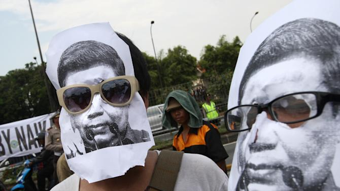 Protesters wear masks of Indonesian President Susilo Bambang Yudhoyono during a protest against the government's plan to raise fuel prices outside the parliament in Jakarta, Indonesia, Tuesday, March 27, 2012. The Indonesian government plans to raise fuel prices by about 33 percent next month to avoid a budget deficit due to expensive fuel subsidies. (AP Photo/Dita Alangkara)