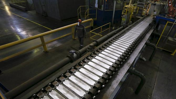 A worker watches aluminium ingots on a conveyor belt at the Rusal Khakassia aluminium smelter outside the town of Sayanogorsk