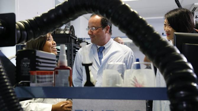 French President Francois Hollande visits the IXBlue company laboratories with French Junior Minister of Small Business, Innovation, and Digital Economy Fleur Pelerin, right, in Marly-le-Roi, near Paris, Thursday, Aug. 8, 2013. (AP Photo/Christian Hartmann, Pool)
