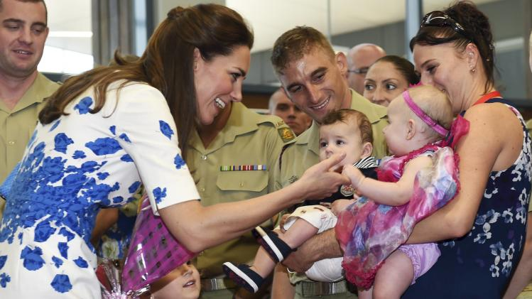 Catherine, Duchess of Cambridge meets six-month-old Alyssa McCabe held by her mother Jillian as she visits the families of service personnel at RAAF Base Amberley