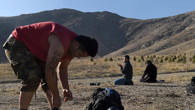 Sporting a tattoo, an Afghan boxing student, Asil Patan, 21 (L) ties the laces of his shoe as trainer Ahmad Nazir, 26, (C) prays before a boxing training session on a hillside of Kabu, December 14, 2014