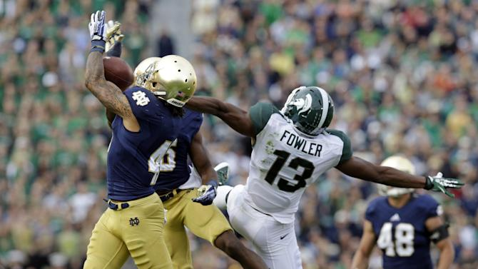 Notre Dame safety Matthias Farley, left, intercepts a pass intended for Michigan State wide receiver Bennie Fowler (13) during the second half of an NCAA college football game in South Bend, Ind., Saturday, Sept. 21, 2013. Notre Dame defeated Michigan State 17-13. (AP Photo/Michael Conroy)