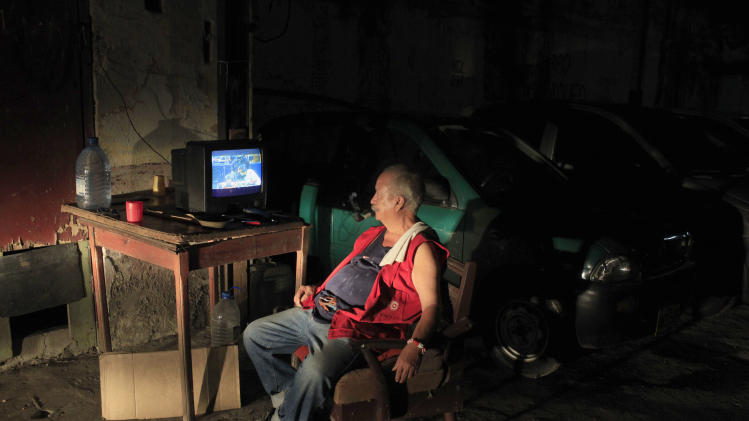 Andres Ortega, who works parking cars, is illuminated by an arriving car as he watches a baseball game between the Atlanta Braves and Washington Nationals that was played in May, on state television in Havana, Cuba, late Sunday, June 30, 2013. Cubans got a rare treat when state TV carried a Major League Baseball game for the first time in more than 50 years, but expressed disappointment when it turned out to be a nearly two-month old match-up without any of the defected Cuban stars whom islanders are most eager to follow. (AP Photo/Franklin Reyes)