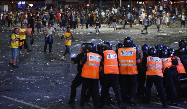 Fans of Argentine soccer team Boca Juniors confront police during riots after celebrations of Boca Juniors Fan Day in Buenos Aires