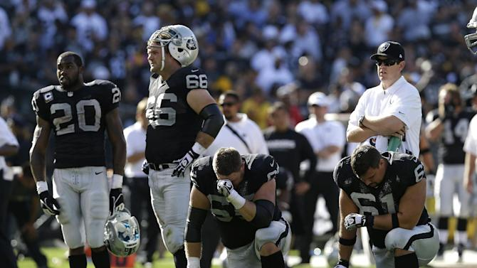Oakland Raiders from left, Darren McFadden, Cooper Carlisle, Mike Brisiel, and Stefen Wisniewski, wait on the field following the injury of wide receiver Darrius Heyward-Bey during the fourth quarter of an NFL football game against the Pittsburgh Steelers in Oakland, Calif., Sunday, Sept. 23, 2012. Oakland won 34-31. Heyward-Bey was taken to a hospital with a neck injury after a helmet-to-helmet hit from Steelers' Ryan Mundy that was not penalized. (AP Photo/Marcio Jose Sanchez)