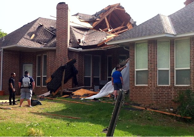 Residents of Edmond, Okla., survey storm damage from a tornado that hit their neighborhood Sunday, May 19, 2013. Forecasters had warned that the middle of the country would see severe weather througho