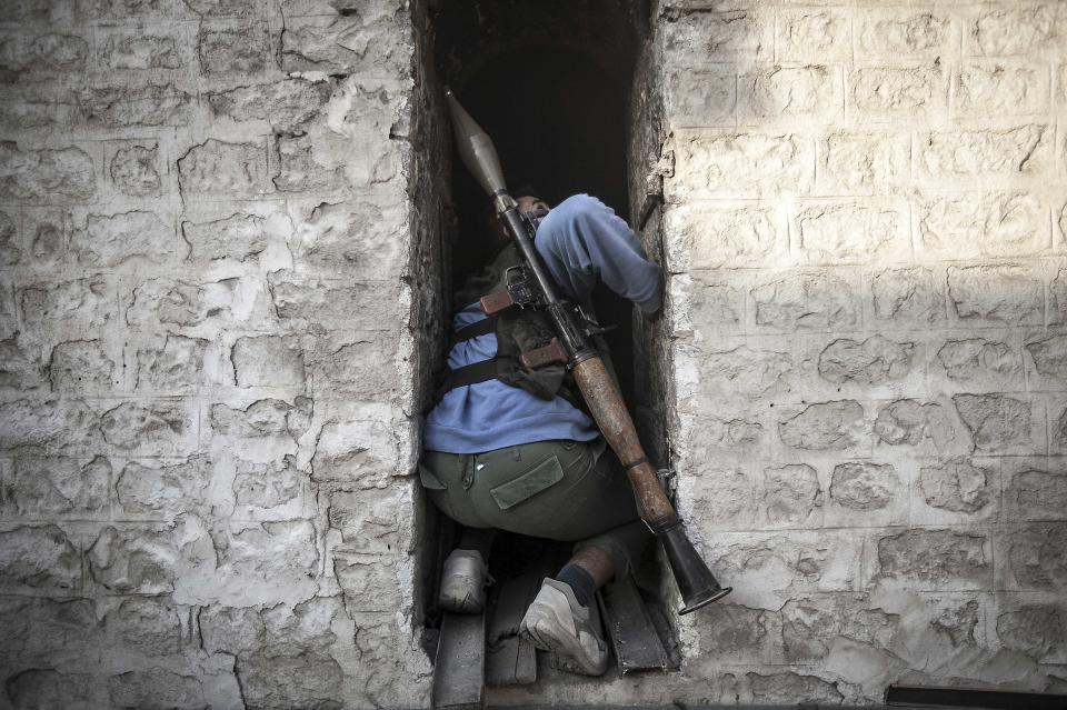 In this Saturday, Nov. 3, 2012 photo, a rebel fighter takes cover as he looks back up at a warplane attacking rebel positions during heavy clashes between rebel fighters and the Syrian army. (AP Photo/Narciso Contreras)