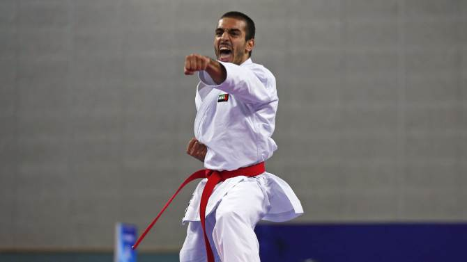 Marwan Abdullah Murad Ahm Almaazmi of the UAE competes against Hong Kong's Cheng Tsz Man Chris in the men's kata bronze medal contest of the karate competition at Gyeyang Gymnasium during the 17th Asian Games in Incheon