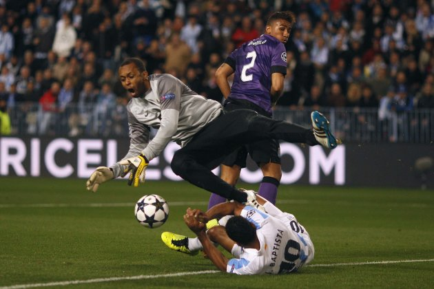Malaga's Julio Baptista fouls Porto's goalkeeper Helton Aruda as he challenges for the ball during their Champions League soccer match in Malaga