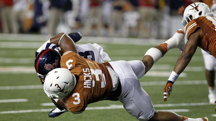 Texas linebacker Jordan Hicks (3) tackles Mississippi running back Jeff Scott (3) during the third quarter of an NCAA college football game Saturday, Sept. 14, 2013, in Austin, Texas. Ole Miss won 44-23