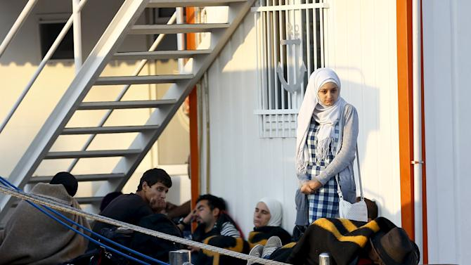 Migrants wait at a Turkish coast guard station near the resort town of Bodrum