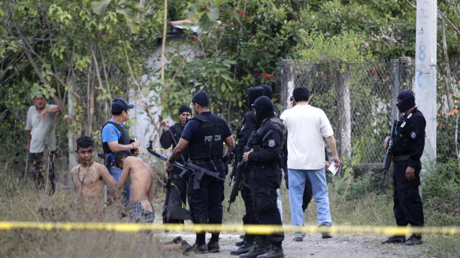 Salvadoran policemen detain suspected gang members in crime scene where six members of 18th. Street Gang were killed in town of Santiago Nonualco