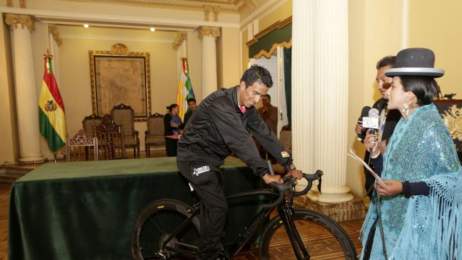 Professional cyclist Oscar Soliz (L) rides a bike that Bolivia's President Evo Morales presented to him as a gift at the presidential palace in La Paz