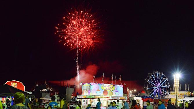 In a Tuesday, Sept. 16 photo, fireworks light up the sky as fairgoers walk around the midway on the opening day of the Lenoir County Fair. The fair will run through Sept. 21. (AP Photo/Daily Free Press, Janet S. Carter )