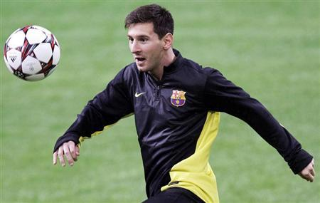 Barcelona's Messi looks at the ball during a training session at the San Siro stadium in Milan