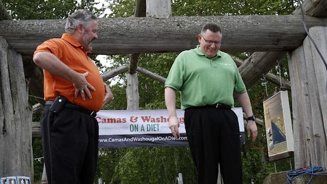 "FILE - In this May 2, 2012 file photo, Washougal Mayor Sean Guard, left, coaxes Camas Mayor Scott Higgins to step on the scales during their weigh-in in Washougal, Wash. The mayors of the two neighboring towns are in a ""Biggest Loser"" style contest to see which of the two communities can lose the most weight. New government projections suggest roughly 42 percent of Americans will be obese by 2030. (AP Photo/Don Ryan)"
