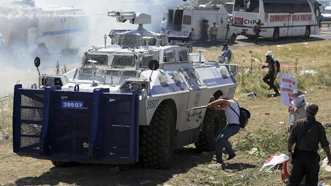 """Protesters clash with riot and paramilitary polices as they fire tear gas and use water cannons to disperse them outside the Silivri jail complex in Silivri, Turkey, Monday, Aug. 5, 2013. Some 275 people - including military officers, politicians and journalists - are facing verdicts in a landmark and divisive trial in Turkey over an alleged conspiracy to overthrow the government. The court has acquitted 21 people accused of plotting to overthrow the Islamist-rooted government in the five-year """"Ergenekon"""" trial and sentenced of up to 47 years or life terms in jails some of the other 254 defendants.(AP Photo)"""