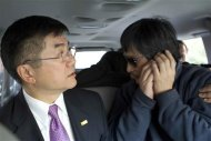 An handout photo from US Embassy Beijing Press office shows blind activist Chen making a phone call