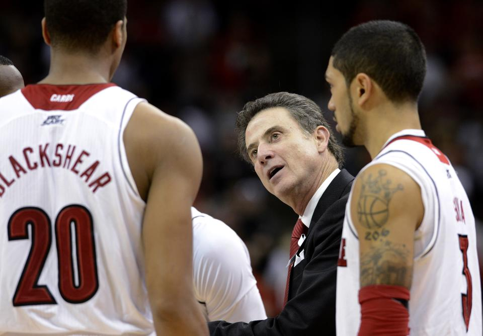 Louisville coach Rick Pitino, center, talks to Wayne Blackshear, left, during the second half of an NCAA college basketball game against South Florida on Saturday Jan. 12, 2013, in Louisville, Ky. At right is Peyton Siva. Louisville defeated South Florida 64-38. (AP Photo/Timothy D. Easley)