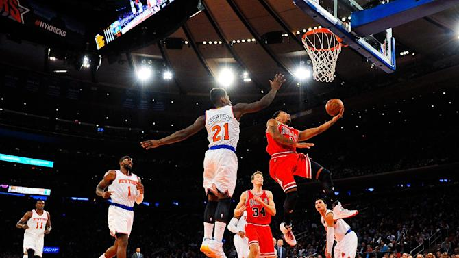Derrick Rose of the Chicago Bulls attempts a lay up under Iman Shumpert of the New York Knicks during their game at Madison Square Garden on October 29, 2014