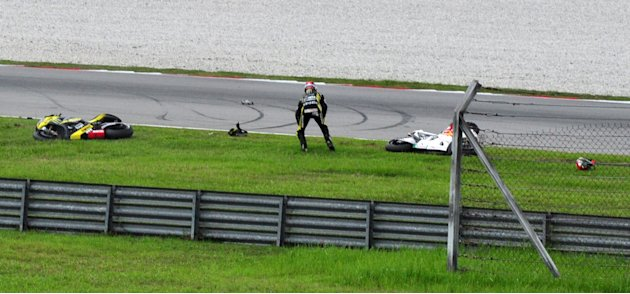Colin Edwards of the U.S., reacts  after the crash involving other two Italy's riders Marco Simoncelli, his motorcycle seen at right, and Valentino Rossi, at the Malaysian MotoGP Grand Prix in Sepang,