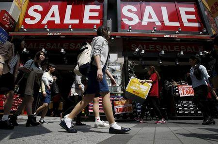 A shop clerk carries a box under sale signboards at a shoes store in Tokyo