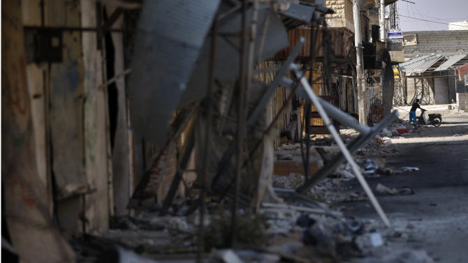 In this Sunday Aug. 5, 2012 photo, a Syrian man is seen in the back as he stands next to his motorcycle by the destroyed shops in the town of Atareb on the outskirts of Aleppo, Syria. (AP Photo)