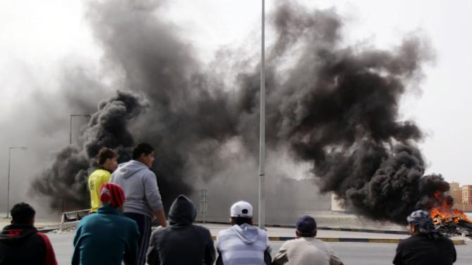 Shiite Bahraini youths burn tires Wednesday, March 16, 2011, near a shopping mall in Malkiya, Bahrain, as they awaited government forces they anticipated would roll into their Shiite Muslim village southwest of the capital of Manama. They said they tried to get to Manama to join anti-government protesters under attack there but found all ways in to the capital closed. (AP Photo/Hasan Jamali)