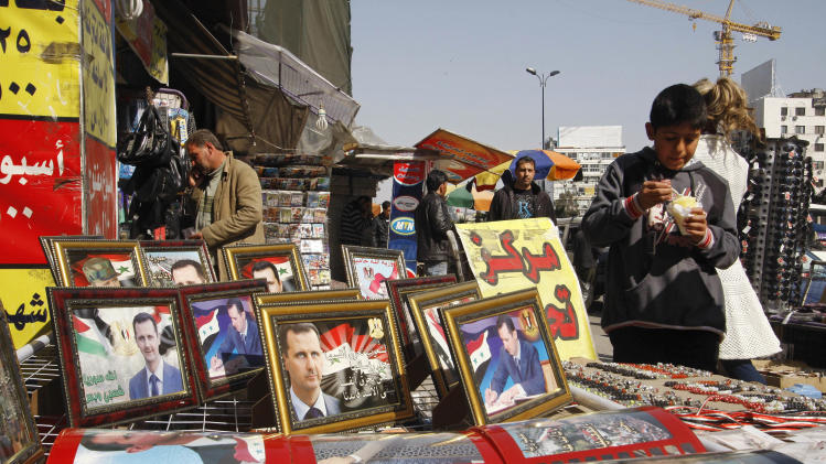 A vendor displays pictures of Syrian President Bashar Assad in Damascus, Syria, Thursday, March 22, 2012. Mounting international condemnation of Bashar Assad's regime and high-level diplomacy have failed to ease the year-old Syria conflict, which the U.N. says has killed more than 8,000 people. (AP Photo/Muzaffar Salman)