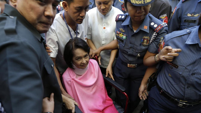 Former Philippine President Gloria Macapagal Arroyo, center, who is currently under hospital arrest, is wheeled into the courtroom of the Sandiganbayan (Anti-graft Court) upon arrival for her arraignment Monday, Oct. 29, 2012 at suburban Quezon city, northeast of Manila, Philippines. Arroyo, who is charged with plunder for allegedly misusing state lottery funds, refused to enter a plea and the anti-graft court entered a not guilty plea on her behalf. (AP Photo/Bullit Marquez)