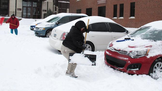 Mindy Tilley, left, and Jennifer Carlock, right, clear the area around their vehicles of snow outside the office where they work after 9 inches fell, Thursday, Feb. 21, 2013, in Topeka, Kan. The two women say they arrived at work in the morning with only a trace of snow on the ground. (AP Photo/John Hanna)
