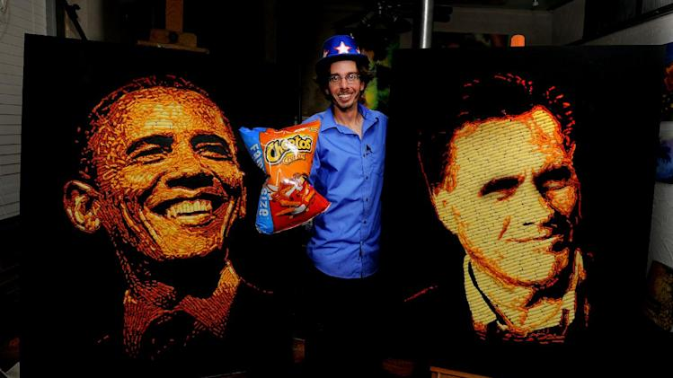 IMAGE DISTRIBUTED FOR CHEETOS - Artist Jason Baalman poses in front of portraits of President Barack Obama and former Gov. Mitt Romney made entirely of more than 2,000 individual Cheetos snacks Tuesday, Oct. 2, 2012, in Baalman's Colorado Springs, Colo., studio.  Today, the Cheetos brand unveiled a new electoral polling model with the unveiling of 3 feet by 4 feet one-of-a-kind Cheetos portraits of the Democratic and Republican presidential nominees – President Barack Obama and former Gov. Mitt Romney. Debuting on Facebook today at 11 a.m. CT, fans are encouraged to vote for their candidate's portrait – made entirely of more than 2,000 individual Cheetos cheese snacks – for a chance to win the actual portrait. (Photo by Jack Dempsey/Invision for Cheetos/AP Images)