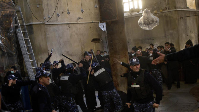 Palestinian police officers intervene in a fight that erupted between Greek Orthodox and Armenian clergymen during the cleaning of the Church of the Nativity in the West Bank town of Bethlehem, Wednesday, Dec. 28, 2011. The two denominations each control sections of the church and fiercely guard their turf. The violence broke out when the sides accused each other of crossing into each other's territory. Similar fights have taken place in past years. (AP Photo/Bernat Armangue)