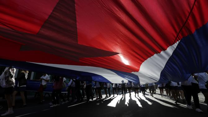 Cuban students carry a giant national flag during a march in Havana