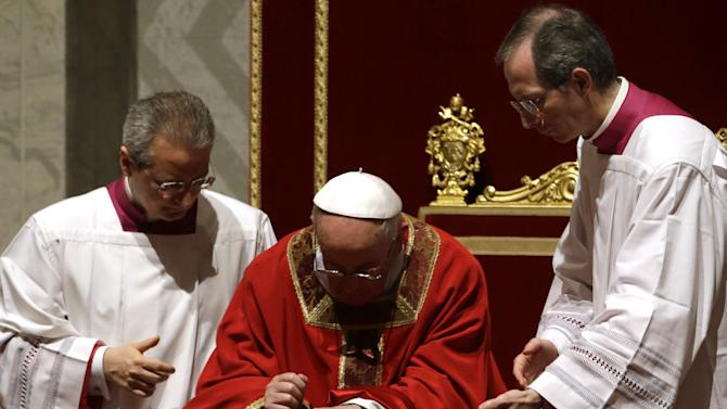 Pope Francis kneels in prayer as he is flanked by his aides, including Mons. Guido Marini, right, during the Passion of Christ Mass inside St. Peter's Basilica, at the Vatican, Friday, March 29, 2013. Pope Francis began the Good Friday service at the Vatican with the Passion of Christ Mass and hours later will go to the ancient Colosseum in Rome for the traditional Way of the Cross procession. (AP Photo/Gregorio Borgia)