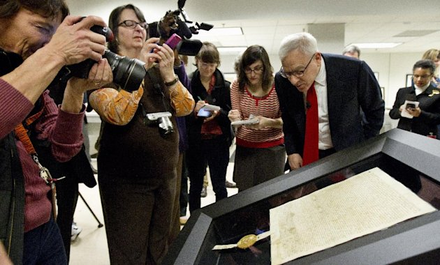 Carlyle Group co-founder and owner of Magna Carta David Rubenstein, right, looks at the 1297 Magna Carta in its new state-of-the-art encasement, Thursday, Feb. 2, 2012, at the National Archives in Washington. (AP Photo/Manuel Balce Ceneta)