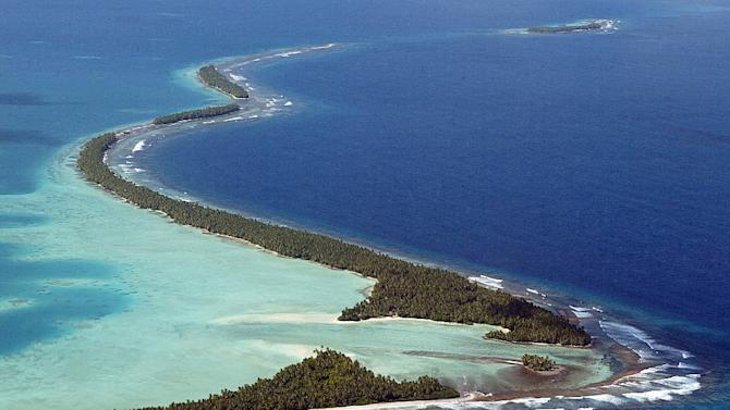 File photo taken in February 2004 shows the South Pacific pounding the coastline of Tuvalu's Funafuti Atoll as king tides caused by climate change threaten the tiny island nation