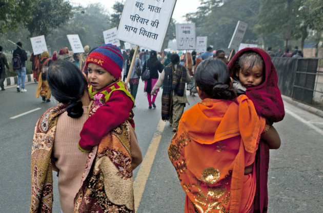 Indian women carry their children as they march during a protest to mourn the death of a gang rape victim in New Delhi, India, Wednesday, Jan. 2, 2013. India's top court said it will decide whether to