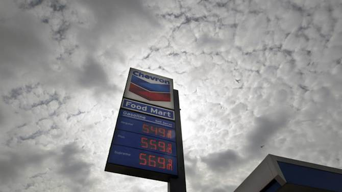 """FILE - In this Tuesday, Oct.  9, 2012, file photo, a Chevron station posts gasoline prices starting at $5.50 per gallon in downtown Los Angeles. Shares of Chevron Corp. plunged Wednesday after the oil giant said its third-quarter earnings are expected to be """"substantially lower"""" than in the second quarter. (AP Photo/Reed Saxon, File)"""