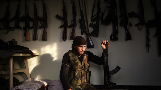 In this Wednesday, Dec. 12, 2012 photo, a Syrian rebel, no name given, prepares for a video interview, at their headquarters in Maaret Ikhwan, near Idlib, Syria. The new Syrian rebel chief, a defected army general who spent months in exile, says he has begun operating inside Syria to unite autonomous anti-regime militias for what he hopes will be the final push against President Bashar Assad. (AP Photo/Muhammed Muheisen)