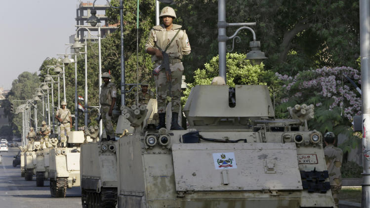 Egyptian army soldiers stand guard on their armored personnel carriers near the presidential palace, in Cairo, Egypt, Thursday, July 11, 2013. Egypt's Muslim Brotherhood vowed Thursday not to back down in its push to restore ousted Islamist leader Mohammed Morsi to power but insisted its resistance is peaceful in an effort to distance itself from more than a week of clashes with security forces. (AP Photo/Hussein Malla)