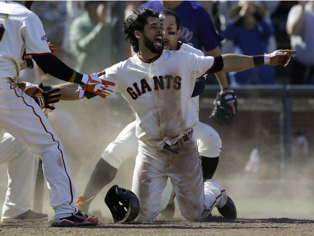 San Francisco Giants' Angel Pagan, center foreground, celebrates with Andres Torres after hitting an inside-the-park two-run home run off Colorado Rockies pitcher Rafael Betancourt during the tenth in