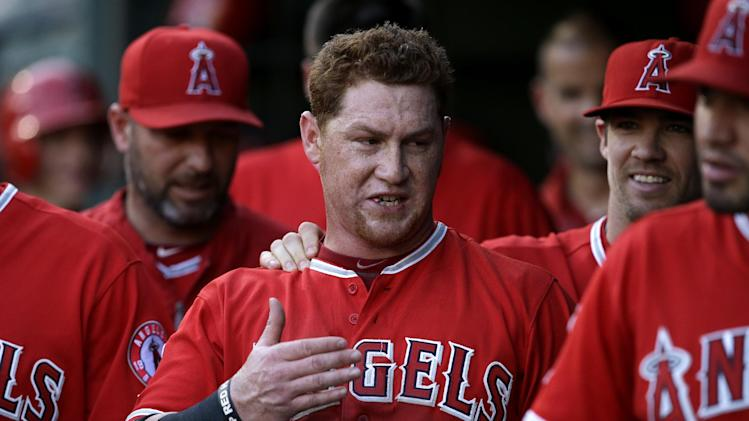 Los Angeles Angels' Kole Calhoun is congratulated in the dugout after scoring on a Albert Pujols sacrifice fly that came off a pitch from Texas Rangers' Colby Lewis in the second inning of a baseball game, Thursday, July 10, 2014, in Arlington, Texas. (AP Photo/Tony Gutierrez)