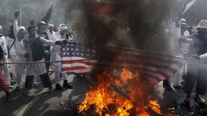 """Muslim protesters burn a U.S. flag during a protest against American-made film """"Innocence of Muslims"""" that ridicules Islam and depicts the Prophet Muhammad as a fraud, a womanizer and a madman, outside the U.S. Embassy in Jakarta, Indonesia, Monday, Sept. 17, 2012. (AP Photo/Dita Alangkara)"""