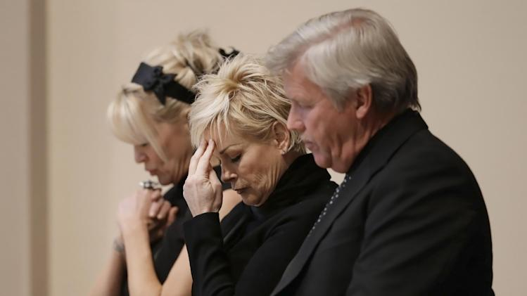 Lorrie Morgan, center, and Bekka Bramlett, left, pray during a memorial service for country singer Mindy McCready on Wednesday, March 6, 2013, in Nashville, Tenn. Both Morgan and Bramlett sang at the ceremony. McCready committed suicide Feb. 17 in Heber Springs, Ark. (AP Photo/Mark Humphrey)